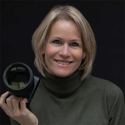 een foto van een vrouwelijke fotograaf met een groene trui, licht blond haar en een camera in haar hand. de vrouw heeft een vriendelijke glimlach op haar gezicht