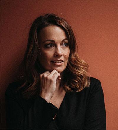 foto van een vrouw tegen een oranje muur
