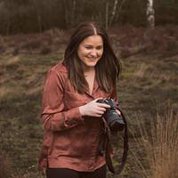een foto van een fotograaf met een camera in haar hand op de heide met een oranje blouse aan