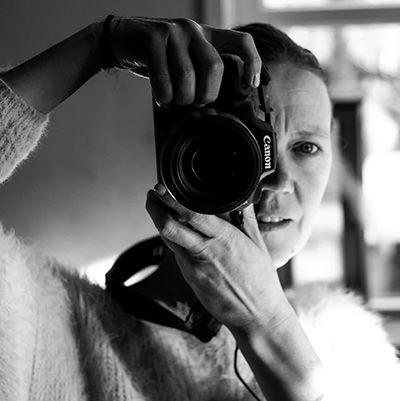 een foto van een vrouw met een camera in haar hand die een foto van zichzelf in de spiegel maakt